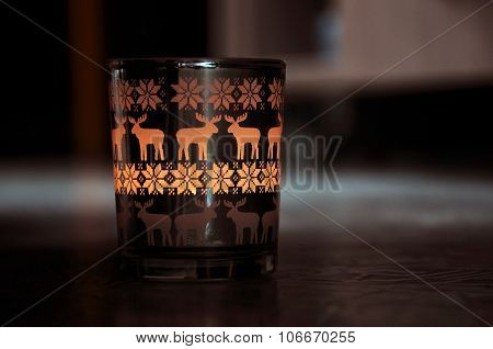 Patterned glass with a burning candle inside