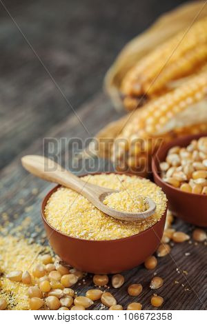 Corn Groats And Seeds In Bowls, Corncobs On Background. Selective Focus