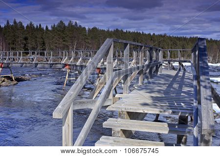 Wooden bridge crosses a low tide river.