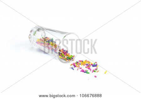 colorful sugar sprinkles fall out from a tiny glass, isolated on a white background, close view
