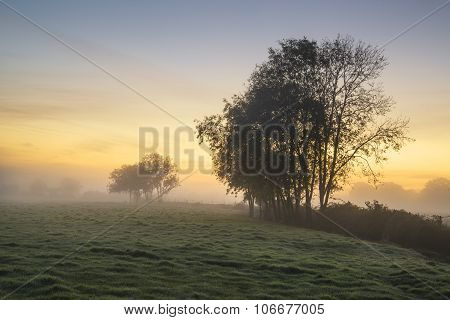 Stunning Vibrant Autumn Foggy Sunrise English Countryside Landscape Image
