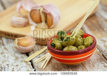 Fresh green olives with garlic in traditional clay bowl on rustic wooden surface