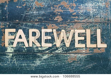 Word farewell written on rustic wooden surface