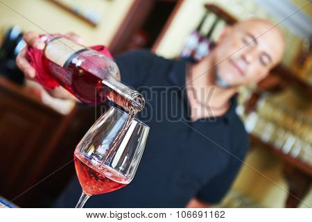 Sommelier barman pouring wine to the glass in the bar