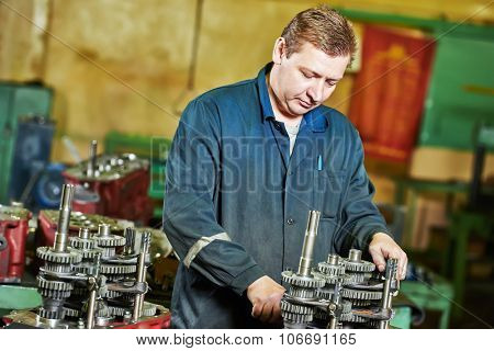 Adult experienced industrial worker assembling the reduction gear box on production line manufacturing workshop