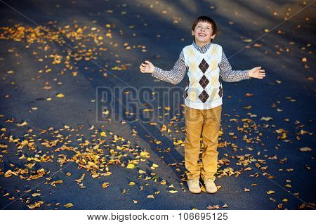 Admiring little boy laughing at beautiful autumn park