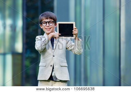 Cute little boy holding empty blackboard