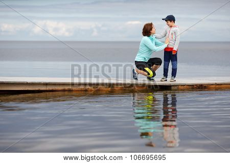 Mother and little son together on wooden jetty