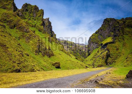 Canyon Pakgil - green grass and moss on fantastic rocks. On canyon there is dirt road. The summer  Iceland