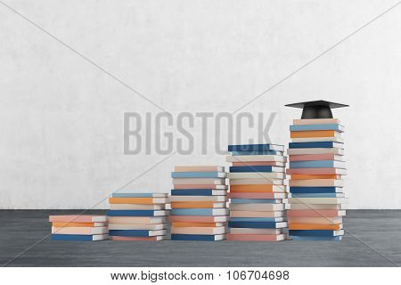 A Stair Is Made Of Colourful Books. A Graduation Hat Is On The Final Step. Concrete Wall And Wooden
