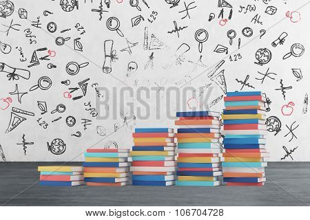 A Stair Is Made Of Colourful Books. Educational Icons Are Drawn On The Concrete Wall. Wooden Floor.