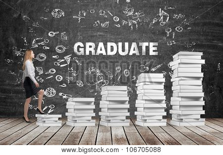 A Woman Is Going Up Using A Stairs Which Are Made Of White Books. The Word Graduate Is On The Black