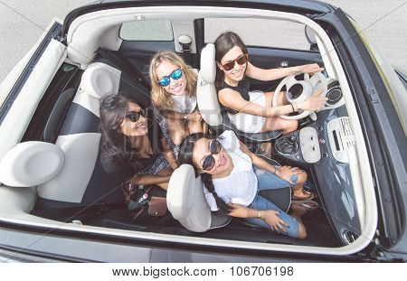 Four Girls Having Fun On A Convertible Car