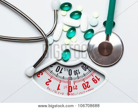 Pills And Stethoscope On Scales. Health Care