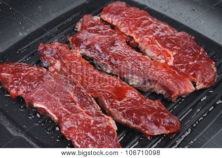 raw bloody beef fillet steaks on black teflon grill plate isolated on white background