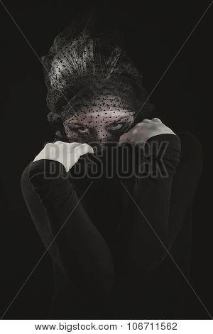 Woman in black peeking mysteriously