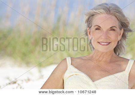 Attraktive elegante Senior Frau sitzt an einem Strand