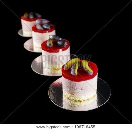 Four small cakes decorated with plum wedges