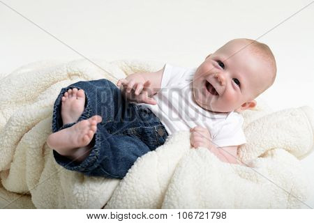 Young Infant With A Hearty Laugh Wearing Jeans