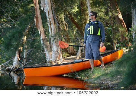 Man With A Kayak In The Forest Wilderness