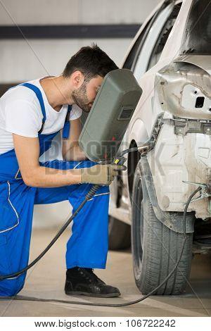 mechanic welding car body in service