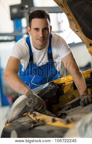 portrait mechanic working on engine on car