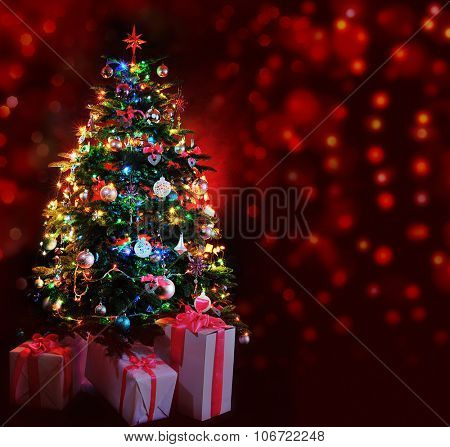 glowing Christmas tree with gifts on dark red background