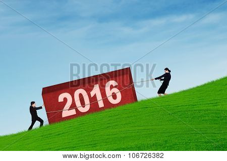 Business Team Carry A Block With Numbers 2016