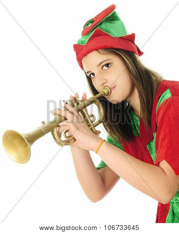 Half-length image of a pretty teen elf looking at the viewer as she tests a toy trumpet.  On a white background.