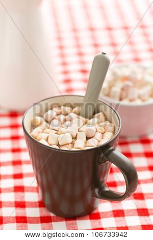 Cocoa drink with marshmallows in mug on checkered tablecloth