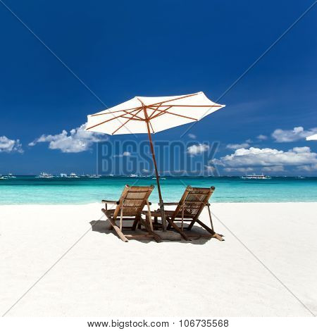 Sun Umbrellas And Wooden Beds On Tropical Beach