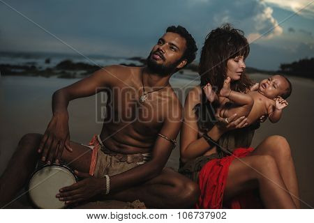 Happy Young Attractive Mixed Race Family with Newborn Baby enjoying in the beach during sunset