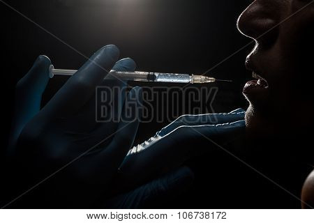 Attractive woman at plastic surgery with syringe in her face
