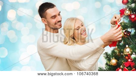 family, x-mas, winter holidays and people concept - happy couple decorating christmas tree at home over blue lights background