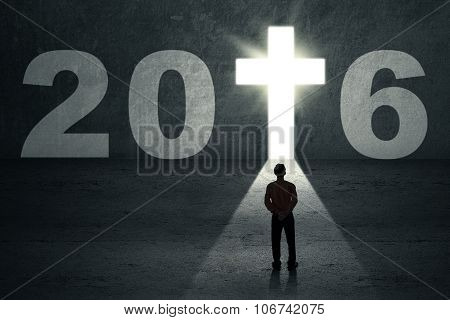Worker Looking At Numbers 2016 And A Cross Symbol