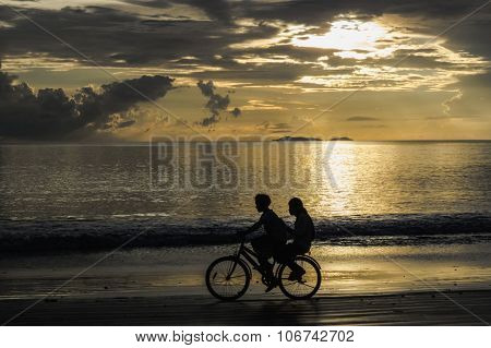 children cycling on the beach on sunset, Thailand