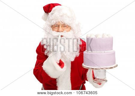 Santa Claus carrying a big cake and holding a finger on his lips isolated on white background