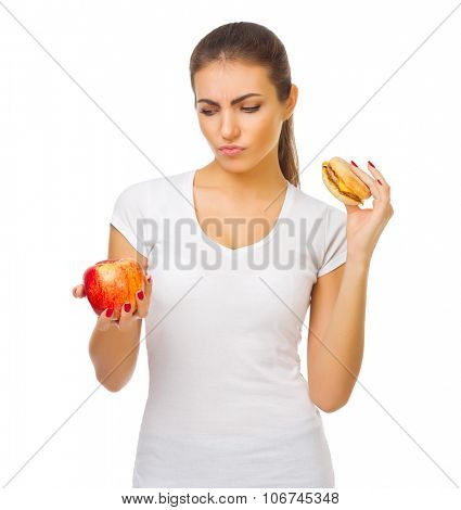 Young doubting girl with apple and hamburger isolated