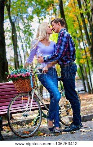 Yong couple with retro bike in the park.