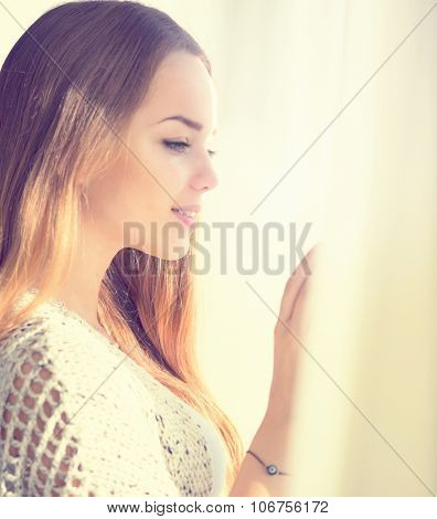 Beauty model girl portrait looking out the window. Young beauty romantic girl looking away, close-up. Beautiful brunette make-up woman in sun light, curtains