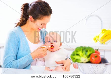 Mother Feeding Her Baby Girl with a Spoon. Mother Giving Food to her adorable Child at Home. Baby food, diet