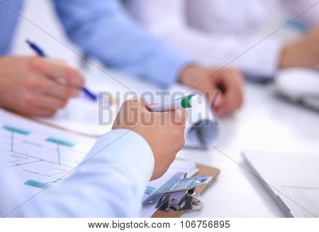 Business people sitting and writting at business meeting, in office