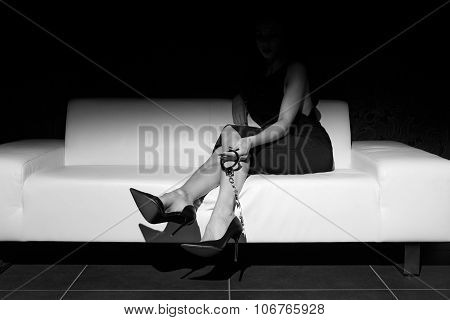 Sexy Woman Holding Handcuffs On Sofa Black And White