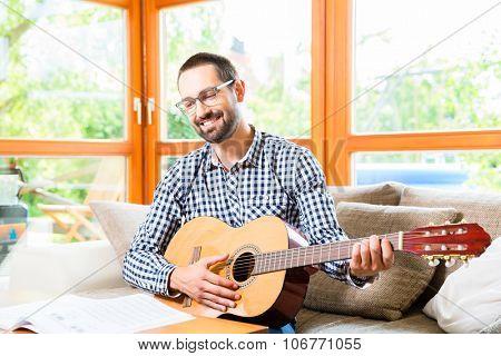 Man playing guitar at home