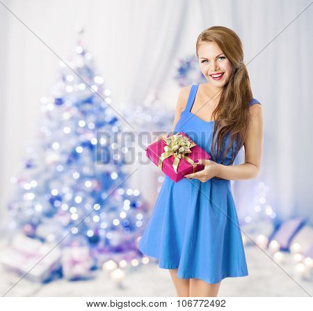Woman Holding Christmas Present Gift Box, Model Girl Posing In Blue Holiday Room, Xmas Tree