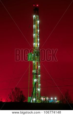A Night View Of A Derrick Drilling.