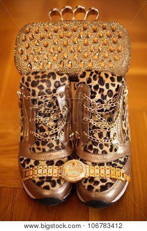 Women Golden Accessories. Luxury Rich Golden Wristwatch And Purse, Leopard Sneakers Shoes On Wooden