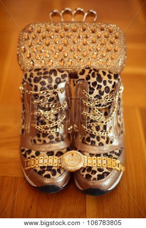 Women's Accessories. Luxury Golden Wristwatch And Purse, Leopard Sneakers Shoes Om Wooden Background