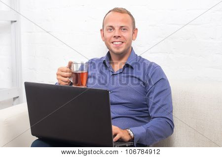 Handsome Businessman Sitting On Couch With Laptop At Home In The Living Room, Looking Camera.