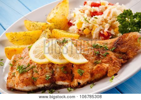 Fish dish - fried fish fillet baked potatoes and vegetables